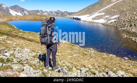 A young man with a big hiking backpack standing next to a clear, navy blue lake hiding between tall mountain peaks. Some of the slopes are covered wit - Stock Photo