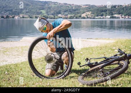 Bike Repair. Man Repairing Mountain Bike. Cyclist man in trouble rear wheel wheel case of accident. Man Fixes Bike near lake in Italy background