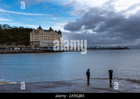 Two young boys paddle in the sea with their shoes on in front of The Grand Hotel at Llandudno and pier at sunset - Stock Photo