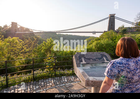 Woman reading the information about Clifton Suspension Bridge,  design by William Henry Barlow and John Hawkshaw, Clifton, Bristol, England, UK - Stock Photo