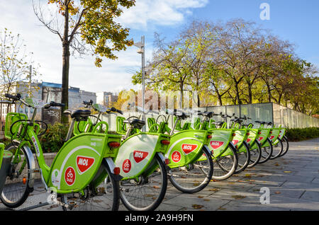 Budapest, Hungary - Nov 6, 2019: Public green bicycles to rent in the center of the Hungarian city. Bike-sharing. Ecological means of transport. Measure in the towns against air pollution. Bikes. - Stock Photo