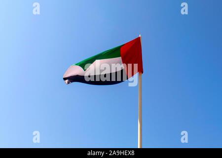 United Arab Emirates flag waving on blue sky background. Close up, isolated. UAE flag. Emirates national day. Flag day - Stock Photo