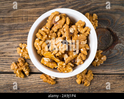 Top view of white cups with walnut, bowls with handful of nuts  on a wooden background - Stock Photo