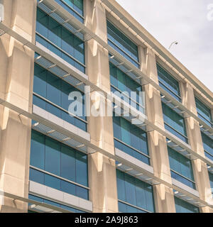 Square frame Modern building facade close up with glass windows and sunlit concrete wall - Stock Photo