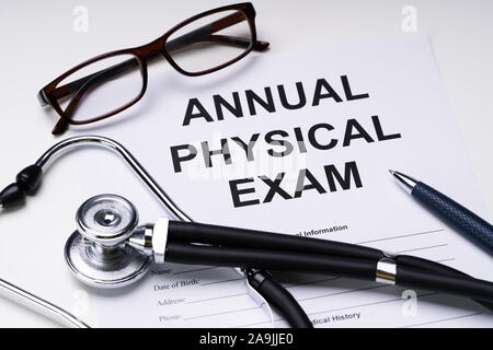 High Angle View Of Annual Physical Exam Form With Stethoscope And Spectacles Over White Desk - Stock Photo