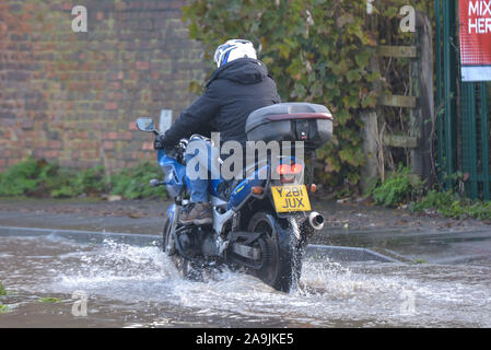 Tewkesbury, Gloucestershire UK. 16th November, 2019. A Motorbike rider lifs his legs as he navigates his way through floods in Tewkesbury town center which has been hit by severe flooding as the River Avon has burst its banks. River levels continue to rise and are expected to peak at over 12 meters above normal river levels late on Saturday afternoon. Pic taken 16/11/2019. Credit: Sam Holiday/Alamy Live News - Stock Photo