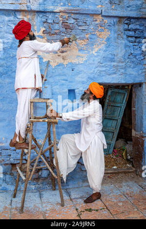 Two men painting the walls on a house in the blue city of Jodhpur, Jodhpur, Rajasthan, India
