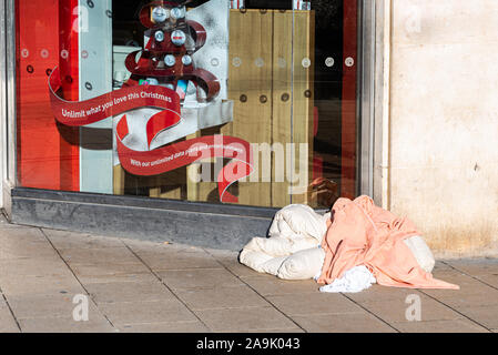 Princess Street, Edinburgh, Scotland, UK, 14/11/2019: discarded bedding next to the high street shop window as Edinburgh prepares for Christmas - Stock Photo