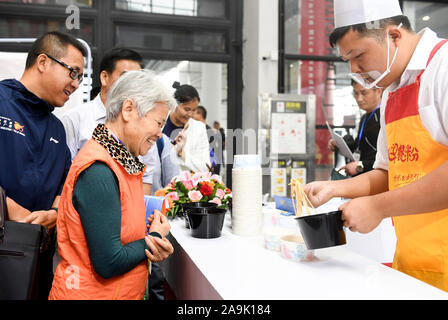 (191116) -- NANNING, Nov. 16, 2019 (Xinhua) -- A staff member makes rice noodle food for visitors at a rice noodle expo held in Nanning, south China's Guangxi Zhuang Autonomous Region, Nov. 16, 2019. The 2019 World Rice Noodle Expo kicked off Saturday at Nanning International Convention and Exhibition Center. Deemed as a major trade fair of the China-ASEAN Expo, the three-day event covers an exhibition area of 10,000 square meters for the exhibition of raw materials, technologies and equipment, condiments, additives, garnishes, packaging, cold-chain logistics, and cooking training, among other - Stock Photo
