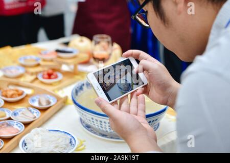 Nanning, south China's Guangxi Zhuang Autonomous Region. 16th Nov 2019. (191116) -- NANNING, Nov. 16, 2019 (Xinhua) -- A visitor takes photos of rice noodle food displayed at a rice noodle expo held in Nanning, south China's Guangxi Zhuang Autonomous Region, Nov. 16, 2019. The 2019 World Rice Noodle Expo kicked off Saturday at Nanning International Convention and Exhibition Center. Deemed as a major trade fair of the China-ASEAN Expo, the three-day event covers an exhibition area of 10,000 square meters for the exhibition of raw materials, technologies and equipment, condiments, additives, gar - Stock Photo