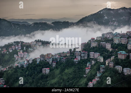 Buildings dotted around the misty mountains during the monsoon season in the Himalayas. Hills around Shimla, Himachal Pradesh, India - Stock Photo