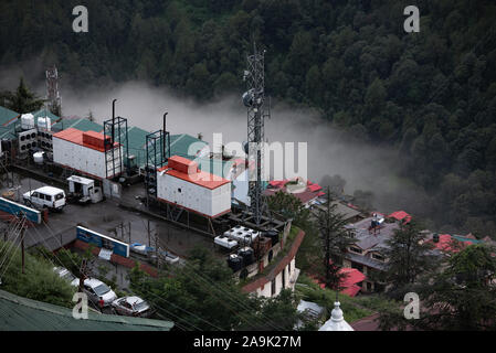 Buildings, mobile masts, telegraph poles on the misty mountains during monsoon season in the Himalayas. Hills around Shimla, Himachal Pradesh, India - Stock Photo