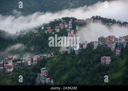 Buildings dotted on the misty mountains during the monsoon season in the Himalayas. Hills around Shimla, Himachal Pradesh, India - Stock Photo