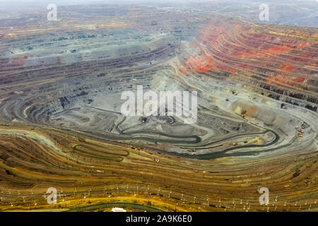 Aerial view of opencast mining quarry with lots of machinery at work - view from above. - Stock Photo