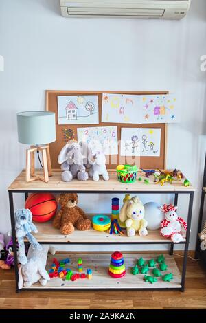 Shelving with lots of  colorful organized toys at kindergarten - Stock Photo