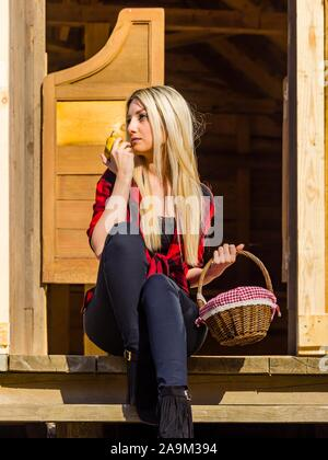 Young woman in village wooden house porch entrance to Western-style bar saloon hand hands hold holding pear fruit and basket - Stock Photo