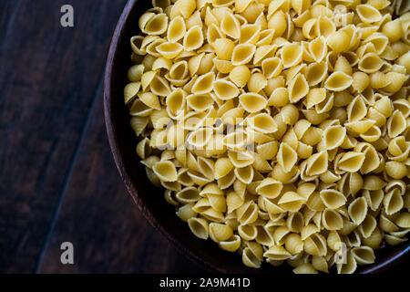 Italian Raw Pasta Shells Conchiglie / Conchiglioni in Wooden Bowl. Ready to Use. - Stock Photo
