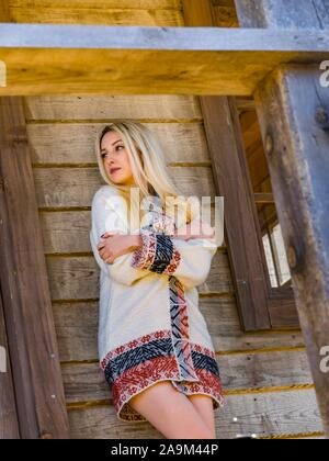 Young woman in village wooden house squeezing hands around body because of cold chilly chill - Stock Photo