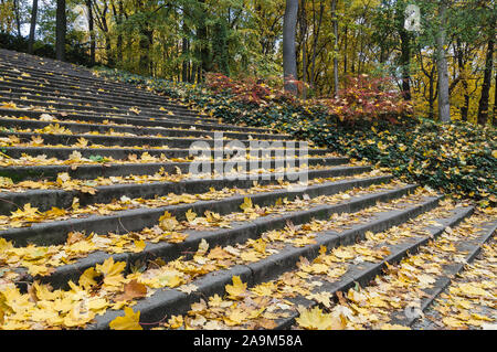 Stone staircase covered in leaves during autumn season in Lazienki park, Warsaw, Poland - Stock Photo