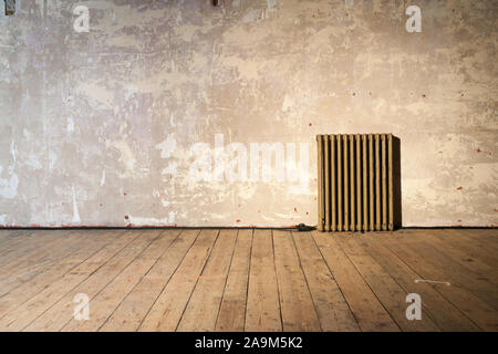 Retro Radiator. A solitary radiator standing in a bare room in need of decorating. - Stock Photo