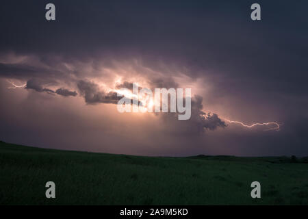 Lightning flashes from cloud to cloud in a supercell thunderstorm over the plains of North Dakota - Stock Photo