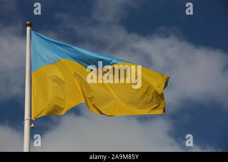 Flag of Ukraine waves on white flagpole against blue sky with white nice clouds - Stock Photo