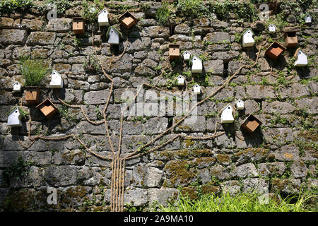 Bird Houses against a wall, Fontaines Petrifiant Gardens, La Sône, France - Stock Photo