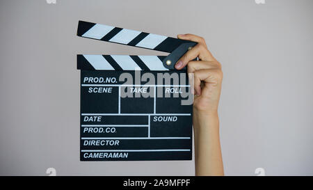 Female hand holding wooden movie clapper. - Stock Photo