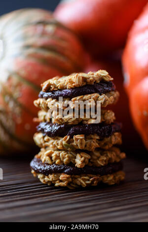 Healthy food concept. Pile of oatmeal pumpkin cookie sandwiches with dark chocolate and bright winter squashes on black background copy space - Stock Photo