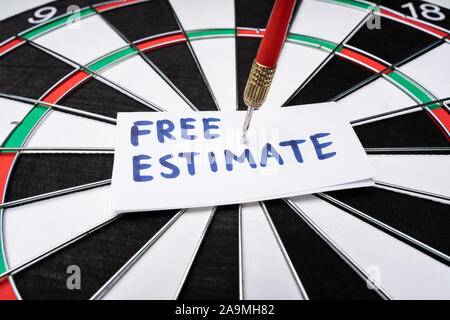 Close-up Of Handwritten Text Free Estimate On Notepaper Stuck At The Center Of Dartboard - Stock Photo