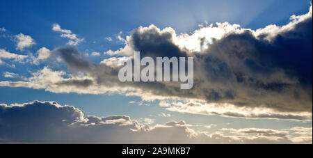 The sun, obscured by a passing cumulo nimbus cloud, throws sunrays up into the blue sky. - Stock Photo