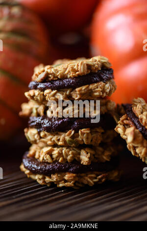 Healthy vegan dessert. Pile of homemade pumpkin oatmeal breakfast cookie sandwiches with dark chocolate and winter squashes on oak board copy space - Stock Photo