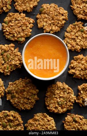 Healthy vegeterian food. Gluten free homemade pumpkin oatmeal breakfast cookies with seeds and pumpkin puree on black background top view - Stock Photo