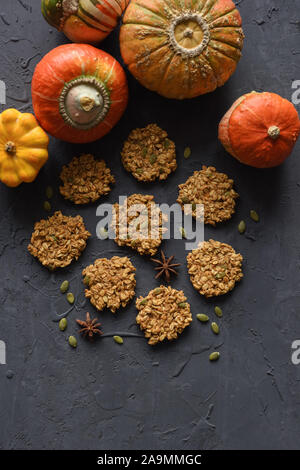 Vegan gluten free baking concept. Flatlay of breakfast homemade oatmeal cookies and winter squashes on black background copy space - Stock Photo