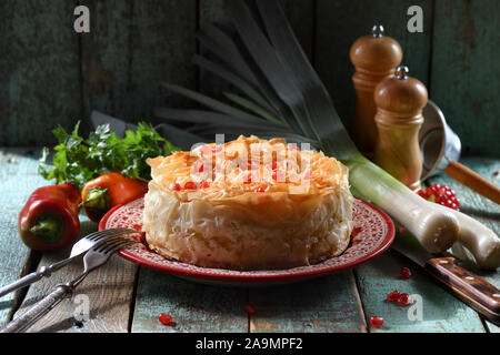 Savory pastry with phyllo dough. Homemade pie on red plate on blue wooden background copy space. Low key still life with natural lighting closeup - Stock Photo