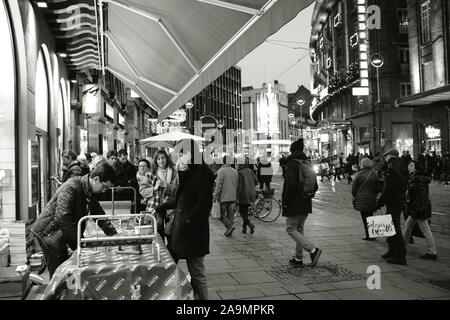Strasbourg, France - Dec 27, 2017: Librarie Library book store Kleber exterior wraping gifts stand during winter holiday witih people waiting in queue to get their gifts prepared - black and white image - Stock Photo