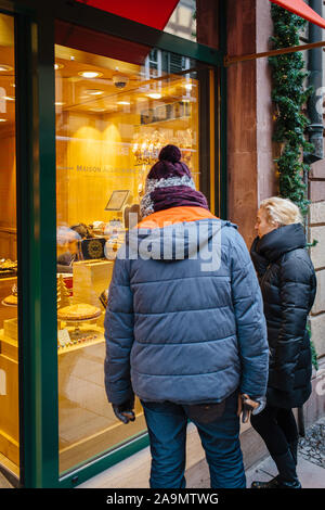 Strasbourg, France - Dec 27, 2017: Rear view of adult couple looking at the showcase of Maison Alsacienne de Biscuiterie bakery store in central Strasbourg on RUe de Dome - Stock Photo
