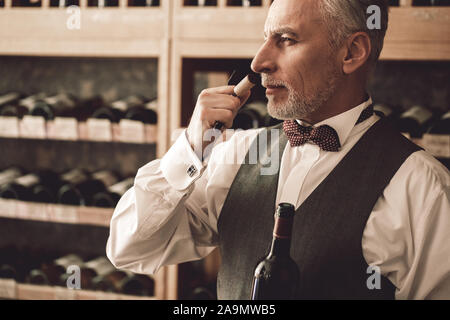 Sommelier Concept. Senior man standing opening wine bottle smelling cork concentrated close-up - Stock Photo