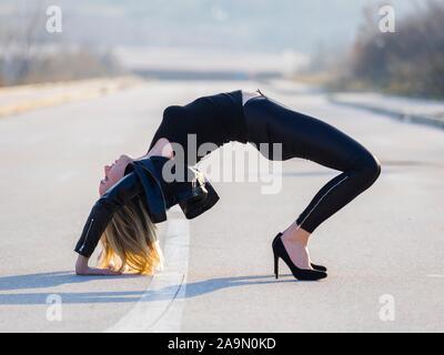 Young woman legs heels maximum effort tension tense posture - Stock Photo