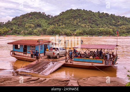 A loaded car ferry on the mighty Mekong River in the picturesque World Heritate Listed town of Luang Prabang in Laos, South East Asia. - Stock Photo