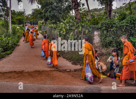 Monks in Saffron Robes in the streets at dawn in the World Heritage Listed town Luang Prabang in Laos in the morning alms giving ceremony or Tak Bak - Stock Photo