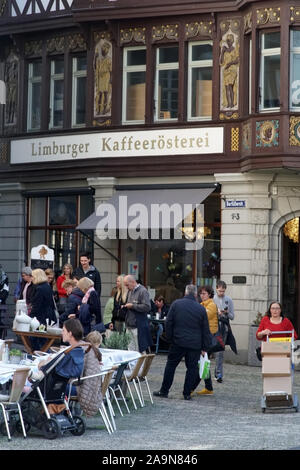 Limburg, Germany - October 12, 2019: The landmarked half-timbered facade of Café Limburger Kaffeerösterei decorated with gold and motifs with guests o - Stock Photo