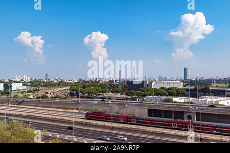 three thunder clouds above the north tel aviv skyline with luna park, ayalon highway, and a train in the foreground - Stock Photo
