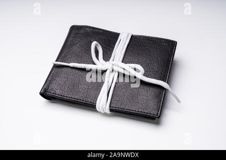 Elevated View Of Black Leather Wallet Tied With White Lace Isolated On White Backdrop - Stock Photo