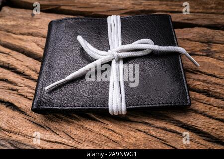High Angle View Of Black Leather Wallet Tied With White Lace On Wooden Background - Stock Photo