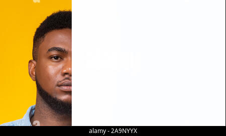 Serious black guy standing behind empty white board - Stock Photo
