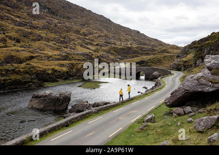 Mother and son walking by the River Loe, narrow road through the Gap of Dunloe valley in the Macgillycuddy's Reeks mountains, Ireland, County Kerry. - Stock Photo
