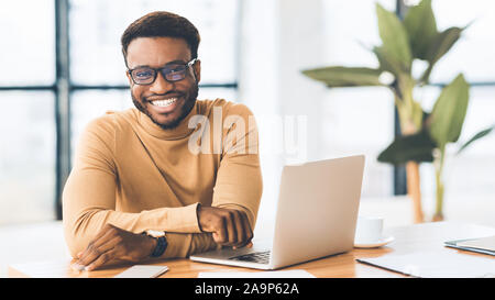Portrait of handsome businessman looking at camera and smiling - Stock Photo