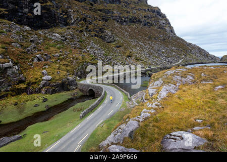 Woman walking by the River Loe, narrow road through the Gap of Dunloe valley, nestled in the Macgillycuddy's Reeks mountains, Ireland, County Kerry. - Stock Photo