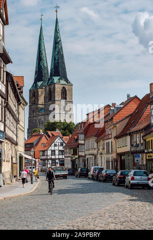 Paved street with colorful traditional historical half-timbered houses in the background the towers of St. Nicholas Church. - Stock Photo
